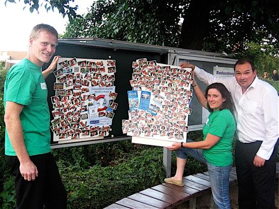 Viele fröhliche Gesichter: Im Schaukasten vor dem Freibadeingang hängt Jowiesen-Betriebsleiterin Silvia Windwehen zusammen mit dem Vorsitzenden Dirk Schütze und Medienwart Enrico Garbelmann die Jowiesenfreunde-Fotos auf.